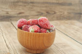 Frozen strawberries in a wooden bowl on wooden background  — Stock Photo