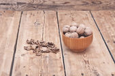 Whole walnuts lying on faded wood with additional nuts in wooden — Stock Photo