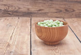 Frozen peas in a wooden  bowl on a wooden table  — Stockfoto