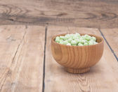 Frozen peas in a wooden  bowl on a wooden table  — Stock Photo