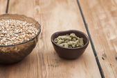 Beer ingredients, hops and malt on wooden table top — Stock Photo