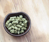 Beer ingredients: toppellets of hops on wooden table — Stock Photo