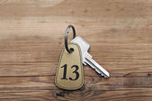 Closeup of an key of room number 13 with key on a wooden desk — Stock Photo