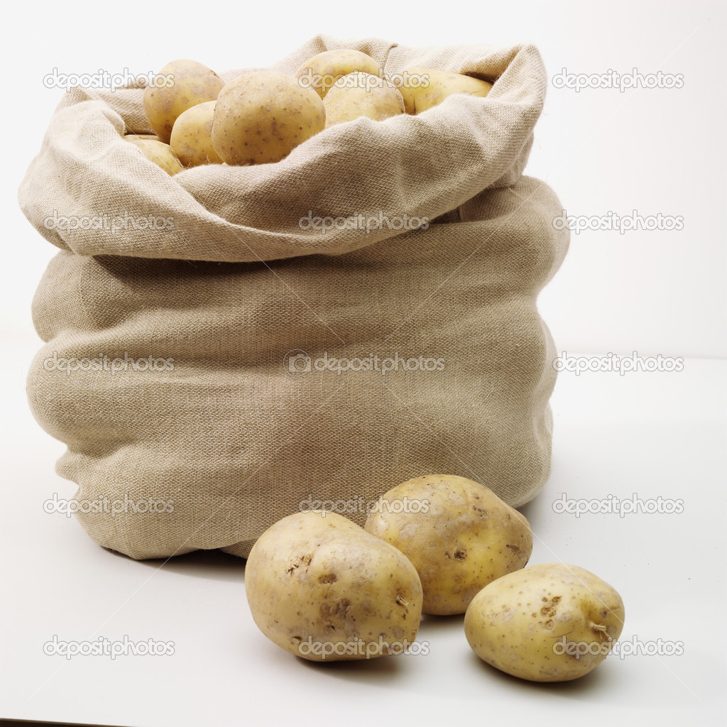 Overflowing bag of potatoes on whit — Stock Photo ...