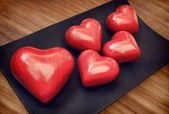 Vintage Red Wooden Valentine Hearts on Brown Woody Table — Stock Photo