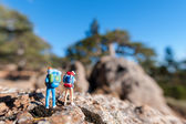 Miniature tourists with backpack — Stock Photo