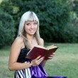 Girl with  book in park. — Stock Photo