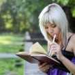 Girl in park with  book — Stok fotoğraf