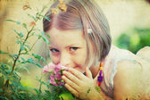 Girl smelling pink roses — Stock Photo