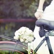 Bride and wedding bouquet on a bicycle — Stock Photo #29019243