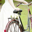 Bride and wedding bouquet on a bicycle — Stock Photo #29019565