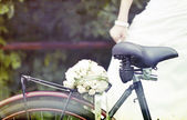Bride and wedding bouquet on a bicycle — Stock Photo
