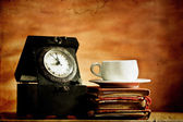 Old clock, coffee and vintage books on grunge background — Stock Photo