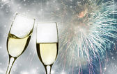 Glasses with champagne against fireworks and clock — Foto de Stock