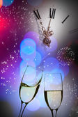 Glasses with champagne against fireworks and clock — Stock Photo