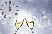 Glasses with champagne against old clock — Stock Photo