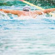Stock Photo: Swimmer performing butterfly stroke