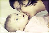 Mother kissing her little baby girl — Stock Photo