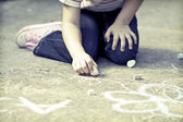 Photo of girl writing with chalk on the schoolyard — ストック写真