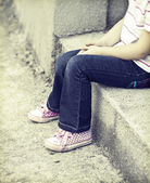 Girl sitting in the schoolyard — Stock Photo