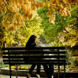 Romantic couple sitting in the autumn park — Stock Photo