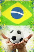 Vintage photo of hands holding soccer ball and Brazil flag — ストック写真