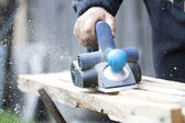Worker's arm sawing wood board — Stock Photo