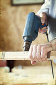 Man's arms drill lath in the workshop — Stock Photo