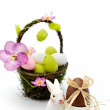 Colorful painted easter eggs in basket and egg cup with chocolate egg — Stock Photo