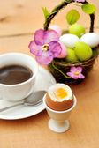 Colorful painted easter eggs in basket, a cup of black coffee and egg cup — Stock Photo