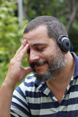 Mature man listening to music with bluetooth headphones — Stock Photo