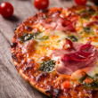 Tasty Italian pizza on wooden background — Stock Photo #13668061
