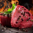 Stock Photo: Raw beef steaks with fire flames