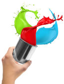 Colored paint splashing out of can — Stock Photo