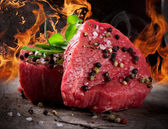 Raw beef steaks with fire flames — Stock Photo