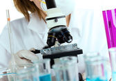 Detail of modern microscope with female researcher — Stock Photo