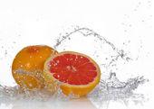 Grapefruit with splashing water — Stock Photo