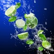 Limes in water splash — Stock Photo