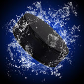 Hockey puck in splashing water — Stock Photo