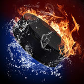 Hockey puck in fire flames and splashing water — Stock Photo