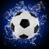 Soccer ball in splashing water — Stock Photo