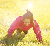 Pretty woman exercising on a meadow — Stock Photo