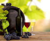 Wine bottle and glasses on wooden table — Stock Photo