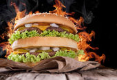 Delicious hamburger with fire flames — Stock Photo