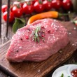 Raw beef steak on wooden table — Stock Photo #44676111