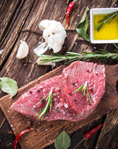 Raw beef steak on wooden table — Stock Photo