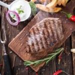 Beef steak on wooden table — Stock Photo #44686725