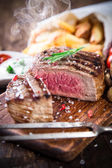 Beef steak on wooden table — Stock Photo