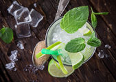 Fresh mojito cocktail on wooden table — Stock Photo