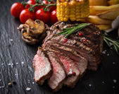 Tasty beef steak on wooden table — Stock Photo